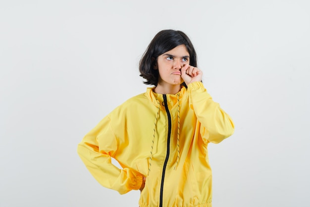 Young girl putting hand on waist, clenching fist in yellow bomber jacket and looking dismal