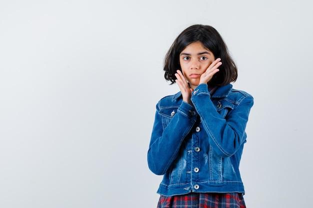 Молодая девушка кладет руки возле лица в клетчатой рубашке и джинсовой куртке и выглядит красиво. передний план.