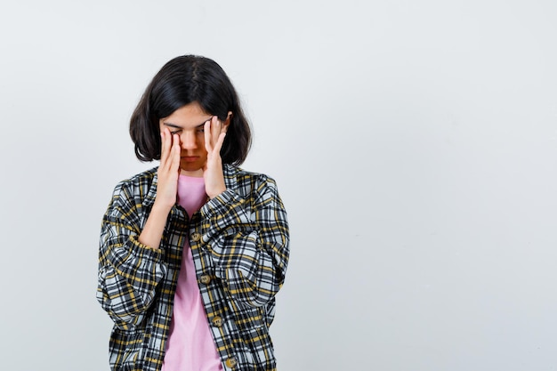 체크 셔츠와 분홍색 티셔츠를 입고 눈을 감고 피곤해 보이는 어린 소녀가 얼굴에 손을 대고 관자놀이를 문지릅니다.