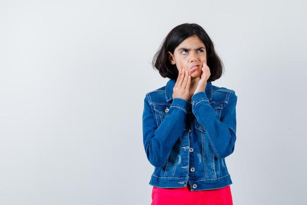 Молодая девушка кладет руки на лицо, растягивает лицо в красной футболке и джинсовой куртке и выглядит взволнованно. передний план.