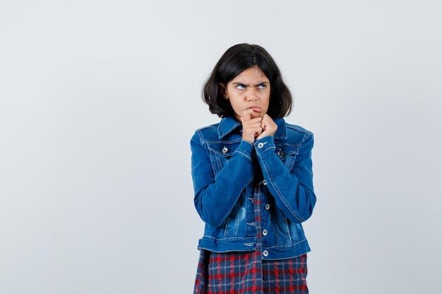 어린 소녀가 손을 입에 대고 체크 셔츠와 진 재킷을 입고 진지하게 생각하고 있습니다. 전면보기.