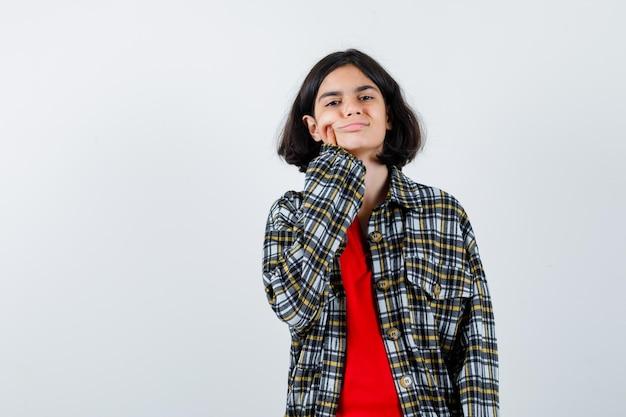 Giovane ragazza che mette il dito indice sulla guancia in maglietta rossa e camicia a quadri e sembra carina. vista frontale.