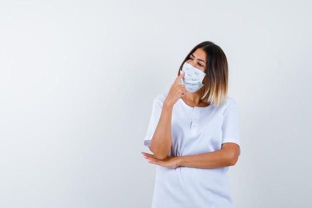 Ragazza che mette il dito indice sulla bocca, tenendo la mano sotto il gomito in maglietta bianca e maschera e guardando pensieroso, vista frontale.