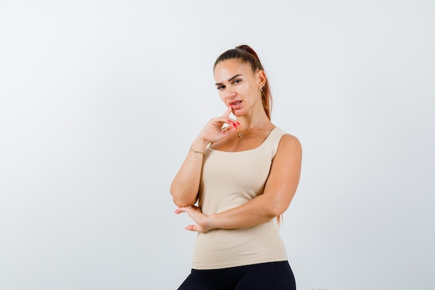 Молодая девушка положила указательный палец возле рта, держа руку под локтем в бежевом топе