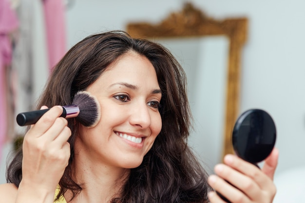 鏡の前で化粧をしている少女がブラシで化粧台を塗る