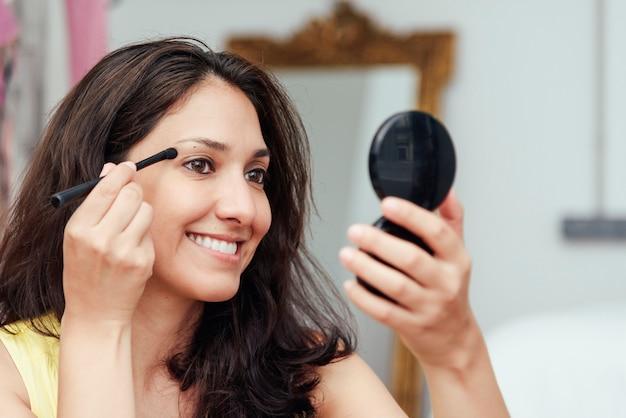 アイラインペンシルで鏡の前で化粧をしている少女
