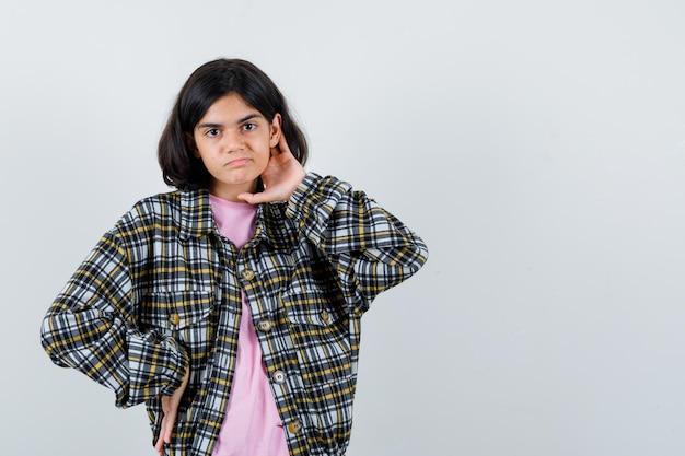 チェックシャツとピンクのtシャツで腰にもう一方の手を保持しながら首に片手を置き、真剣に、正面図を見て若い女の子。