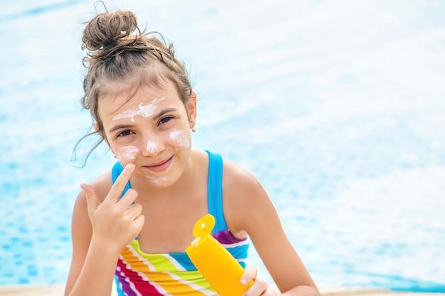 プールのそばの彼女の顔に日焼け止めを置く若い女の子