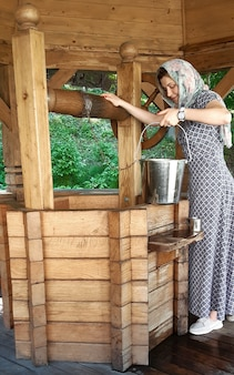 A young girl raises an iron bucket full of water from a wooden old well