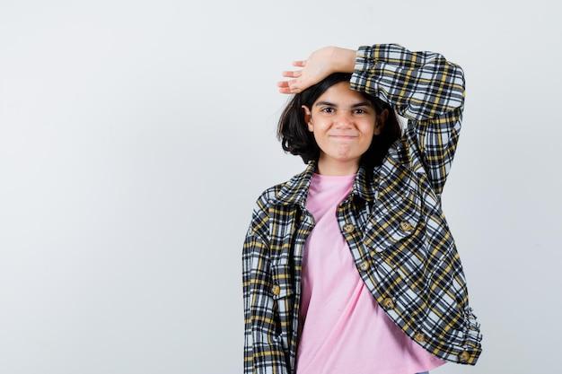 Giovane ragazza che alza il braccio sopra la testa in camicia a quadri e t-shirt rosa e sembra felice. vista frontale.