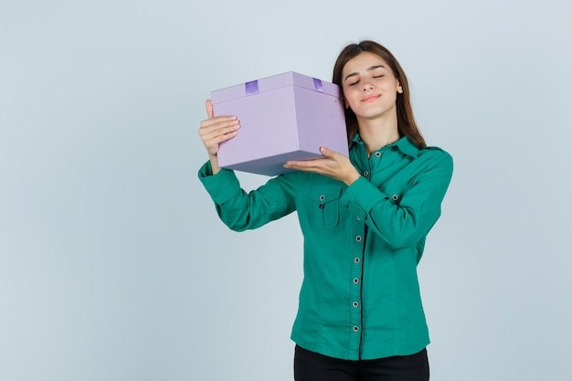 Young girl raising gift box to her shoulder in green blouse, black pants and looking happy. front view.