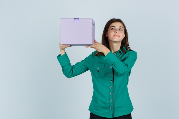 Young girl raising gift box above her shoulder in green blouse, black pants and looking happy , front view.