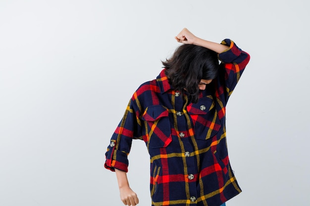 Young girl raising hand above head, bending head in checked shirt and looking cute , front view.