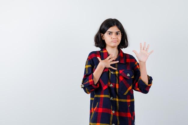 체크 셔츠를 입고 가슴에 손을 대고 진지한 표정을 짓는 동안 무언가를 멈추기 위해 손을 들고 있는 어린 소녀. 전면보기.