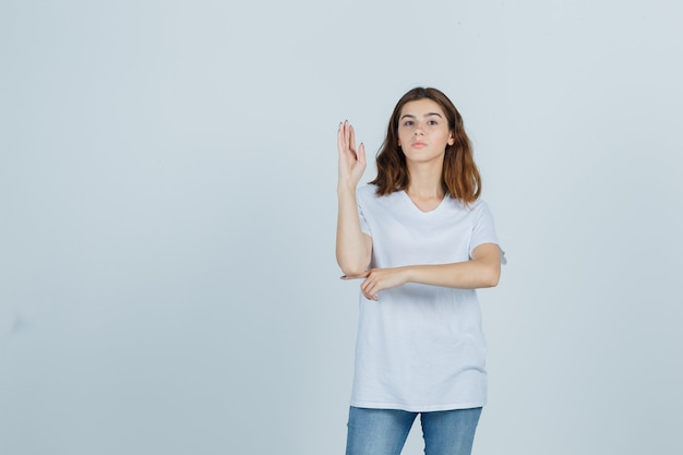 Young girl raising hand in white t-shirt and looking confident , front view.