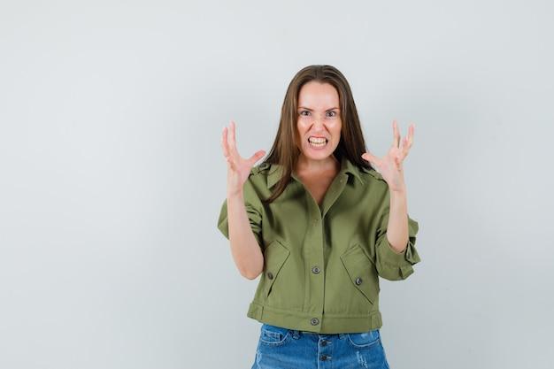 ジャケット、ショートパンツの正面図で積極的に手を上げる少女。
