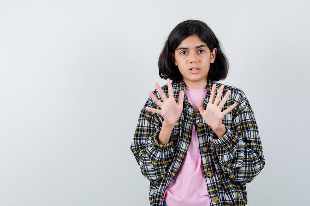 Молодая девушка поднимает руки в позе капитуляции в клетчатой рубашке и розовой футболке и выглядит удивленно.