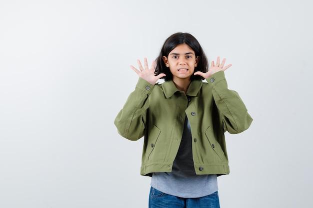 灰色のセーター、カーキ色のジャケット、ジーンズのパンツで降伏のポーズで手を上げて驚いて見える少女。正面図。