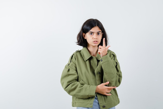 Young girl raising index finger in eureka gesture in grey sweater, khaki jacket, jean pant and looking cute. front view.