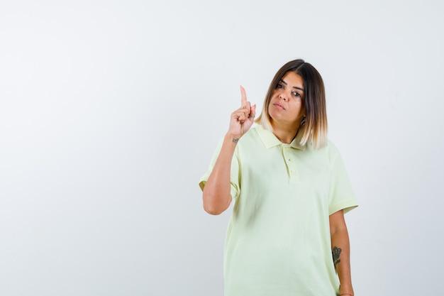 Ragazza che alza il dito indice nel gesto di eureka in maglietta e sembra sensibile, vista frontale.