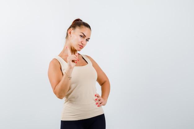 Молодая девушка поднимает указательный палец в жесте эврики, держит руку на талии в бежевом топе, черных штанах и выглядит уверенно, вид спереди.