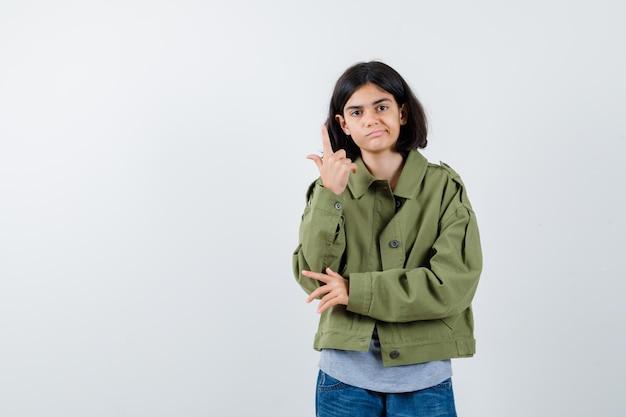 회색 스웨터, 카키색 재킷, 진 바지를 입은 팔꿈치에 손을 잡고 현명하게 보이는 전면 뷰를 유레카 제스처로 집게 손가락을 올리는 어린 소녀.