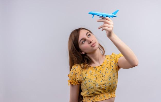 Ragazza che alza l'aereo di modello e lo esamina sulla parete bianca isolata con lo spazio della copia