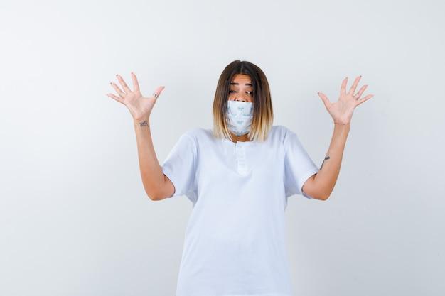 Молодая девушка поднимает ладони в жесте капитуляции в белой футболке, маске и выглядит испуганной. передний план.