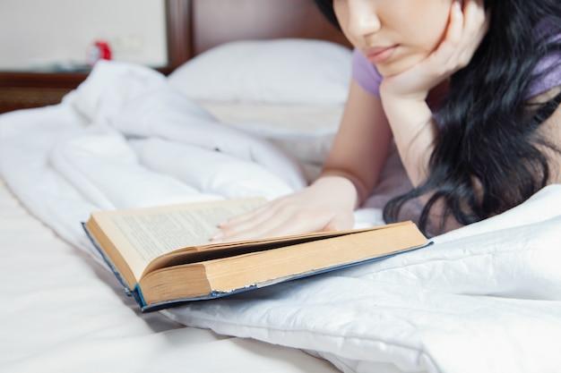 ベッドで本を読んでいる少女
