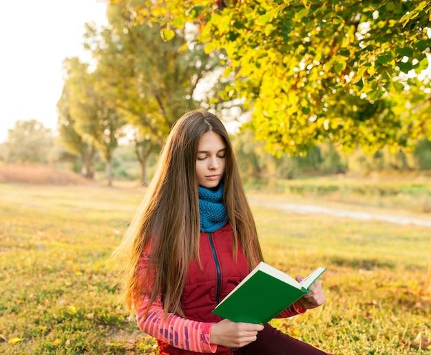 Молодая девушка читает книгу в осеннем парке