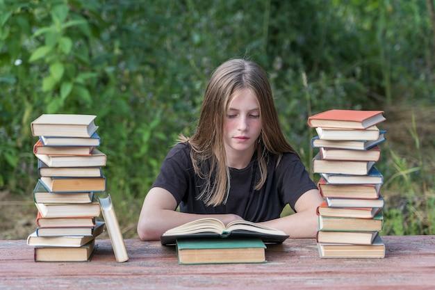 어린 소녀도 서의 스택과 함께 나무 테이블에 정원에서 책을 읽고. 가정 교육 개념