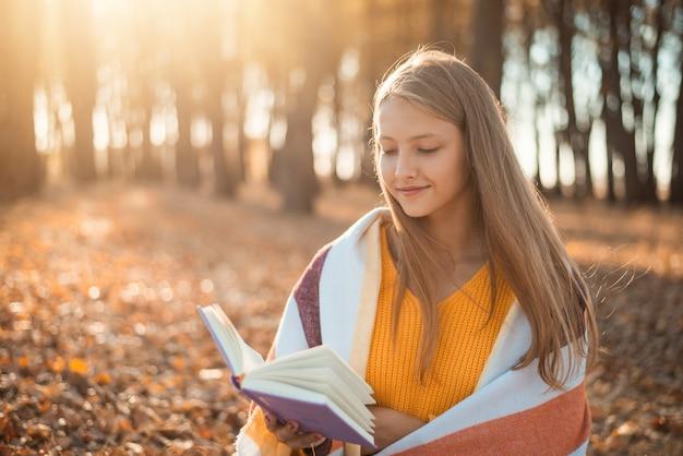 밝은 태양을 배경으로 가을 공원의 벤치에 앉아 책을 읽는 어린 소녀