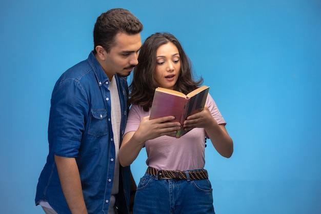 Молодая девушка читает старую книгу со своим партнером.