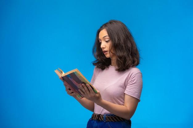 Молодая девушка читает старую книгу.