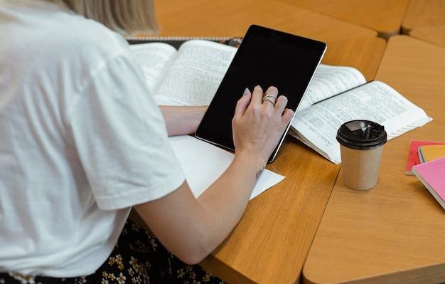 Молодая девушка читает в библиотеке