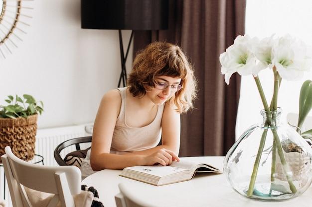 Маленькая девочка, читающая книгу за белым столом в столовой. квартира жилая