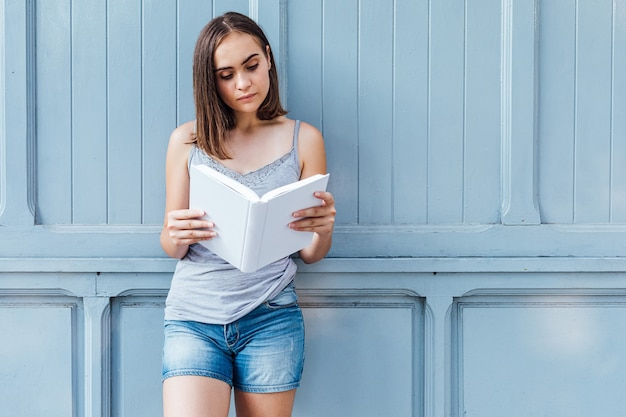 Young girl reading a book on blue gray background