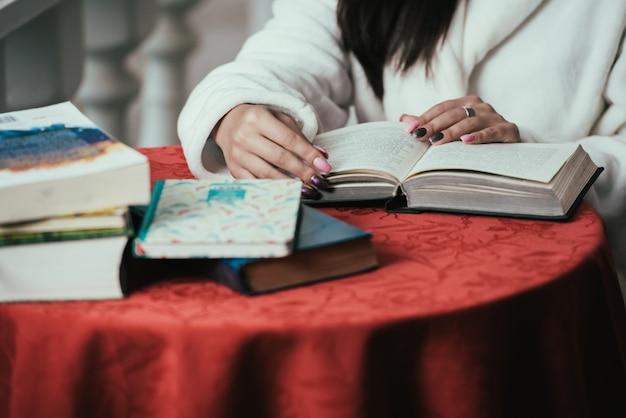 バルコニーに座って晴れた日にコーヒーを飲みながら若い女の子の読書。