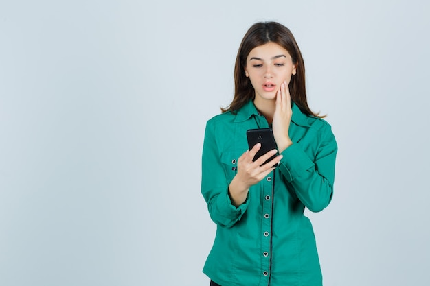 Ragazza che legge i messaggi sul telefono, tenendo la mano sulla guancia in camicetta verde, pantaloni neri e guardando concentrato, vista frontale.