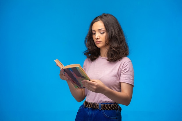 Young girl reading an old book and looks serious