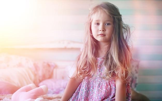 若い女の子が本を読む娘と一緒の若い女の子がベッドに座っています。庭のそばの村の夏の家。村の若い母と娘の残り。