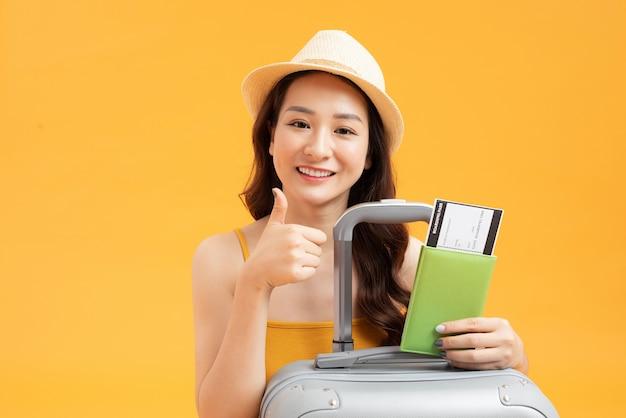 黄色の背景にスーツケースとパスポートを持って旅行する準備ができて若い女の子。夏