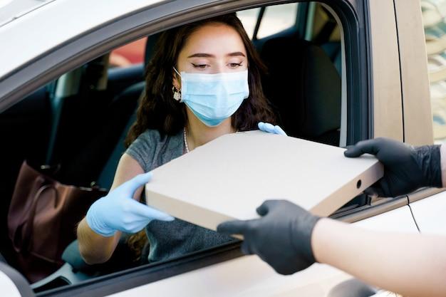 Молодая девушка получает коробку из-под пиццы в машине с медицинской маской и перчатками