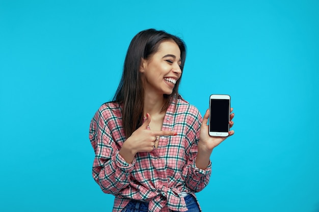 Young girl recommends device or app points at mockup screen of smartphone