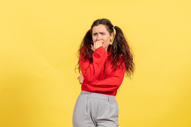 Young girl in red blouse biting her nails on yellow