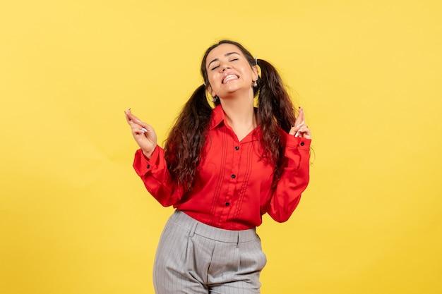 Giovane ragazza in camicetta rossa incrociando le dita sentendosi eccitata sul giallo