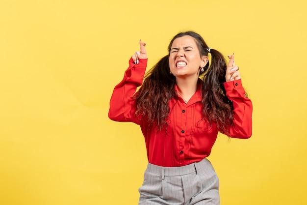 Giovane ragazza in camicetta rossa in posa incrociando le dita sul giallo