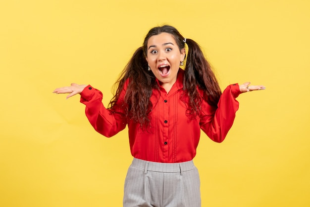 Giovane ragazza in camicetta rossa in posa con espressione eccitata su giallo