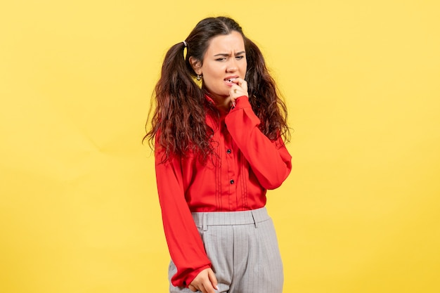 Young girl in red blouse thinking nervously on yellow