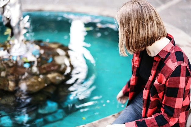 Young girl in red checkered shirt sitting near the fountain.